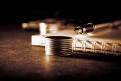 企业、财务或者投资概念 在支票簿或笔记本和钢笔,计算器前面的硬币 黑暗的被定调子的backg 免版税库存照片