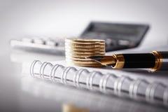 企业、财务或者投资概念 硬币、支票簿或笔记本和钢笔,计算器 奶油被装载的饼干 免版税库存照片