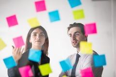 企业、起动、计划、管理和人概念-在贴纸的愉快的创造性的队文字在办公室玻璃板在方式下 免版税库存照片