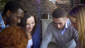 企业、起动和人概念-与计算机的愉快的创造性的队和文件夹谈论项目在共有的顶楼 股票视频