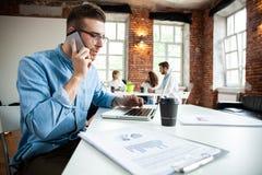 企业、起动和人概念-愉快的商人或创造性的男性办公室工作者有计算机拜访的 库存图片