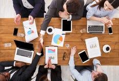 企业不同种族的握手 繁忙的人民在办公室,木桌顶视图工作 库存图片