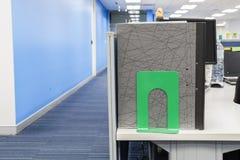 企业与绿色钢书挡的文件夹堆在办公桌上 免版税库存照片