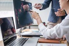 企业与计算机,膝上型计算机,讨论一起使用和分析图表与储蓄图数据的队伙伴股票市场贸易 库存照片