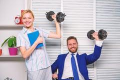 企业严格的小组 健康习性在办公室 男人和妇女提高重的哑铃 强的强有力的经营战略 库存图片