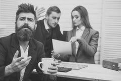 企业争吵 有胡子的人在有希望的面孔拿着杯子,上司,工友,背景的同事 事务 库存照片
