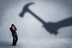 企业人举行锤子概念的害怕阴影手 免版税库存照片