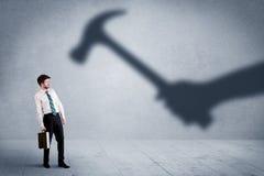 企业人举行锤子概念的害怕阴影手 免版税库存图片