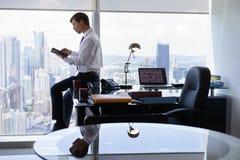 企业人在片剂个人计算机读新闻早晨 免版税库存图片