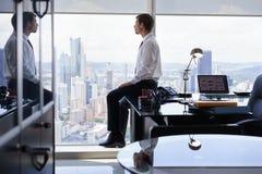 企业人坐看在办公室窗口外面的书桌 免版税库存照片