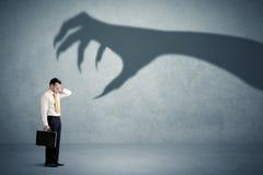 企业人害怕一个大妖怪爪阴影概念 免版税图库摄影