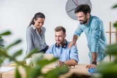 年轻企业同事一起与膝上型计算机一起使用在办公室 免版税库存图片