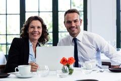 企业同事画象使用膝上型计算机的,当开会议时 图库摄影