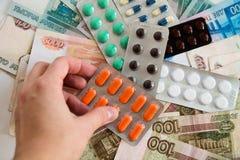 企业和医疗保健概念,拿着在俄国钞票背景的手药片 库存照片