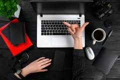 企业和技术题目:妇女的手显示姿态的一件黑衬衣的反对背景膝上型计算机在书桌 库存照片
