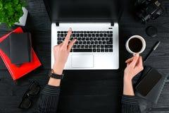 企业和技术题目:妇女的手显示姿态的一件黑衬衣的反对背景膝上型计算机在书桌 免版税库存照片