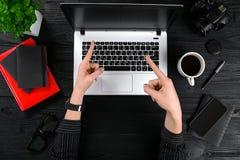 企业和技术题目:妇女的手显示姿态的一件黑衬衣的反对背景膝上型计算机在书桌 图库摄影