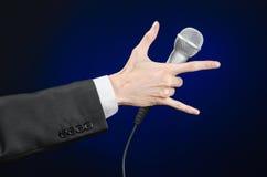 企业和讲话题目:拿着在灰色深蓝被隔绝的背景的黑衣服的人一个话筒在演播室 库存照片