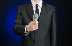 企业和讲话题目:拿着在灰色深蓝被隔绝的背景的黑衣服的人一个话筒在演播室 库存图片
