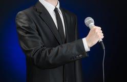 企业和讲话题目:拿着在灰色深蓝被隔绝的背景的黑衣服的人一个话筒在演播室 免版税库存照片