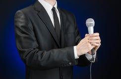 企业和讲话题目:拿着在灰色深蓝被隔绝的背景的黑衣服的人一个话筒在演播室 免版税库存图片