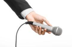 企业和讲话题目:拿着在被隔绝的白色背景的黑衣服的人一个灰色话筒在演播室 图库摄影