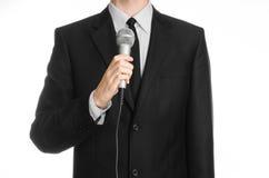 企业和讲话题目:拿着在被隔绝的白色背景的黑衣服的人一个灰色话筒在演播室 免版税库存照片