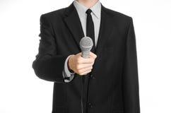 企业和讲话题目:拿着在被隔绝的白色背景的黑衣服的人一个灰色话筒在演播室 库存图片