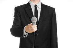 企业和讲话题目:拿着在被隔绝的白色背景的黑衣服的人一个灰色话筒在演播室 免版税库存图片