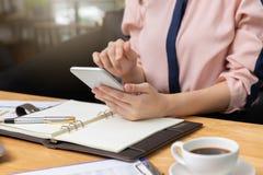 企业和财务概念,使用巧妙的电话的女实业家和谈论销售分析图在咖啡店 免版税库存图片