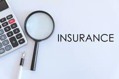 企业和财务概念 计算器、放大镜和笔顶视图在白色背景写与保险 库存图片
