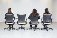 企业坐三名视图妇女的林后方 免版税库存图片