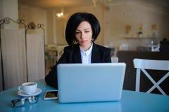 企业夫人在研究膝上型计算机的黑衣服穿戴了 免版税图库摄影