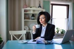 企业夫人在研究膝上型计算机的黑衣服穿戴了 图库摄影