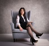 企业夫人:在一把灰色扶手椅子的一个母上司反对灰色墙壁背景 库存照片