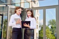 37企业夫人 办公室工作人员 有电子选项的两个女孩 免版税库存图片