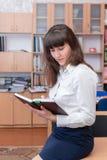 37企业夫人 年轻美丽的女孩在有文件的办公室 免版税库存图片