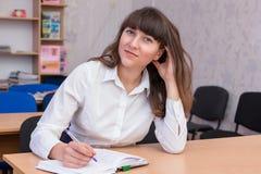 37企业夫人 年轻美丽的女孩在有文件的办公室 库存照片