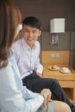 企业夫妇微笑和坐床在旅馆客房 免版税库存图片