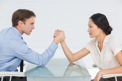 企业夫妇武器角力在书桌 免版税库存照片