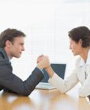 企业夫妇武器角力在办公桌 免版税库存照片