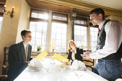 企业夫妇预定的食物在餐馆桌上 免版税库存图片