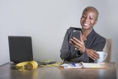 企业夹克工作的年轻可爱和愉快的成功的黑人美国黑人的妇女快乐在办公室膝上型计算机使用机动性 免版税图库摄影