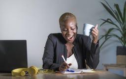 企业夹克工作的年轻可爱和愉快的成功的黑人美国黑人的妇女快乐在采取笔记的办公室膝上型计算机 免版税库存图片