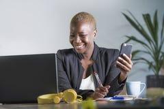 企业夹克工作的愉快的成功的黑人美国黑人的妇女快乐在采取笔记的办公室膝上型计算机使用手机 库存照片