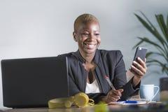 企业夹克工作的愉快的成功的黑人美国黑人的妇女快乐在采取笔记的办公室膝上型计算机使用手机 免版税图库摄影