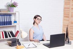 企业女孩坐在办公室纸文件夹的一台计算机 库存照片