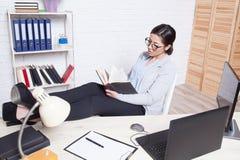 企业女孩坐在办公室纸文件夹的一台计算机 免版税库存照片
