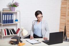 企业女孩坐在办公室纸文件夹的一台计算机 免版税图库摄影