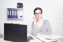 企业女孩坐在办公室纸文件夹的一台计算机 免版税库存图片